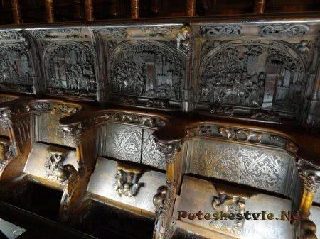 Сценки из жизни людей на спинках скамей в соборе