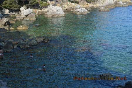 Отдыхающие купаются среди скал в Ллорет-де-Мар