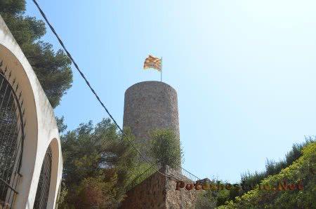 Испанский флаг на старинной башне в Ллорет-де-Мар
