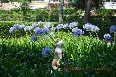 Маленькая статуя в окружении цветов Сада Святой Клотильды