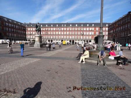 Уставшие туристы отдыхают на лавке в Мадриде
